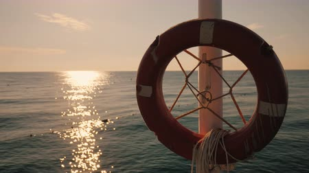 lifebuoy : Lifebuoy hanging on the background of the sea at sunrise. Morning at the sea Stock Footage