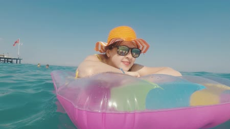 colchão : Attractive woman in an orange hat floats in the sea on an inflatable mattress Stock Footage
