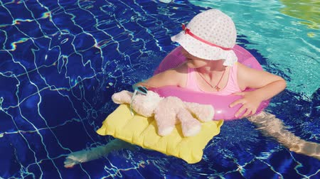 gyerekes : Funny girl in a swimsuit and panama bathes on the inflatable circle with a pink hare in sunglasses in the pool. Joint rest with your favorite toys