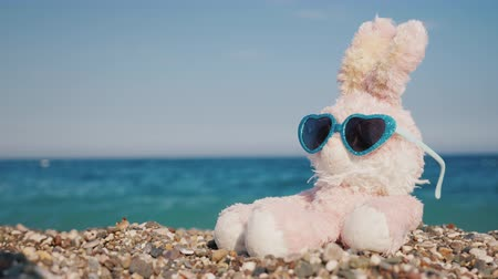 peluş : Plush rabbit in sunglasses sunbathing on the beach