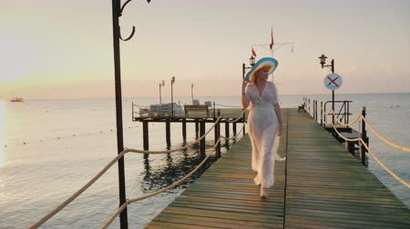 breathing fresh air : A woman in a pair and hat walks on the pier in the early morning. Breathes in the fresh air.