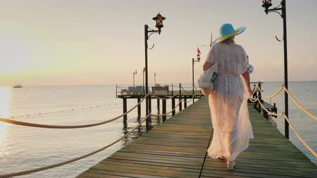 breathing fresh air : Back view: A woman in a pair and hat walks on the pier in the early morning. Breathes in the fresh air. Stock Footage