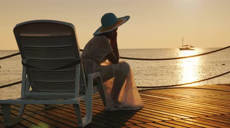 hayran olmak : A woman looks at the sunrise over the sea. Sits on a sunbed, in the distance a fishing boat is visible. Scenic dawn landscape Stok Video