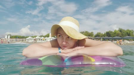 colchão : A young woman in a straw hat is floating on an inflatable mattress on the seashore Stock Footage
