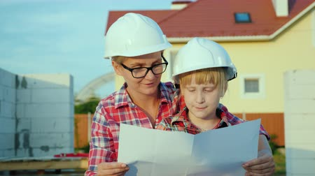 kask : A woman in a helmet with a child looks at the drawing of the house. Are standing side by side on the construction site. Dream of own house concept