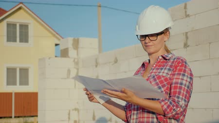 supervisor : A female engineer is studying a drawing. It stands on the construction site of a small cottage