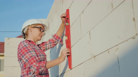 hard hat : A woman engineer checks the quality and accuracy of building a wall in the house. Quality control on the construction concept Stock Footage