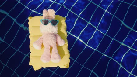 colchão : A pink bunny in sunglasses is floating on an inflatable mattress in the pool. Children and childrens toys
