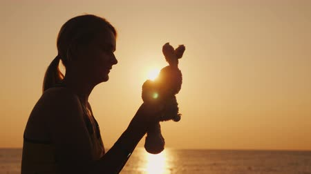 dětinský : Silhouette A woman is playing with a toy bunny at dawn. Remember childhood