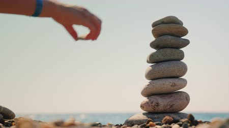 attainment : Build a tower of pebbles against the background of the sea. Equilibrium and meditation concept