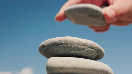 attainment : The hand puts the stone in the tower. Balance and balance concept Stock Footage