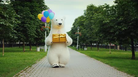 долл : A large polar bear walks down the street, carries balloons and a box with a gift. Birthday gifts and a cool party concept Стоковые видеозаписи