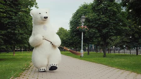 vassoura : A bear cleaner sweeps the street. He holds a broom in his paws. Cleanliness in the city concept