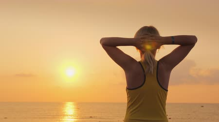 hayran olmak : Fitness woman admiring the sunrise over the sea. Freshness, beauty and health concept