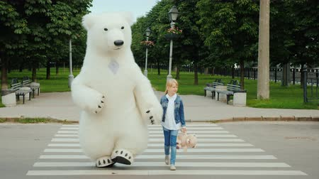 долл : The girl takes over the paw on the pedestrian crossing of a large polar bear. Safety driving concept Стоковые видеозаписи