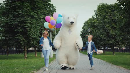 tlapky : Mom and daughter and a polar bear are having fun along the street. Childrens holiday concept