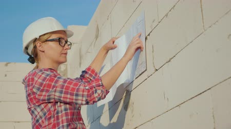 helm : Successful female architect examines a house drawing on a construction site Stockvideo