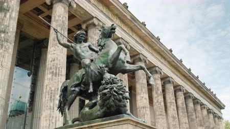 копье : Berlin, Germany, May 2018: Sculpture of a rider with a spear at a defeated lion at The building of the Old National Gallery, built in the late 19th century in the style of an ancient temple Стоковые видеозаписи
