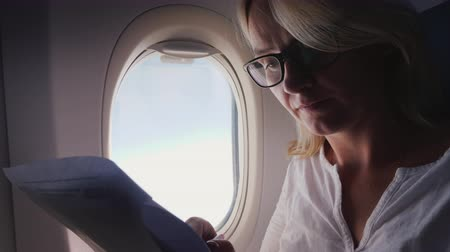 paper airplane : Business woman is reading documents on the plane. Business and Travel