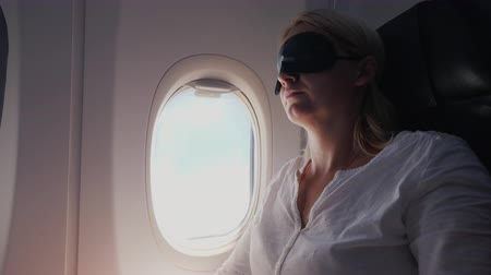 minder : A young woman with a dark bandage in her eyes sleeps in the cabin of a passenger aircraft. Traveling with comfort Stok Video
