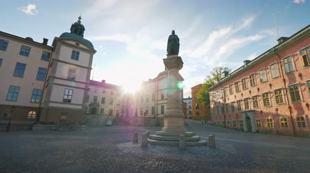 stockholm : Jarl Birger Square, with a monument to the founder of Stockholm and the Palace of Wrangel. The sun shines beautifully from behind buildings