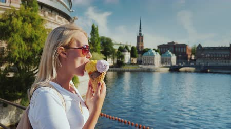 stockholm : A woman with appetite eats a tasty ice cream on the street of Stockholm