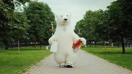 tlapky : Successful shopping, a polar bear walks in the park with packages for shopping Dostupné videozáznamy