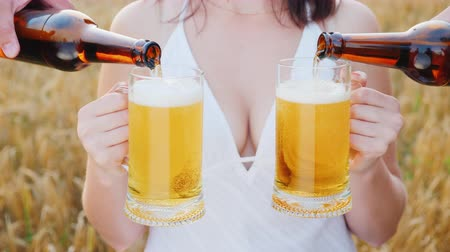 göğüs : An attractive woman with a beautiful breast holds two glasses of beer, on both sides she is poured a cool drink. In the background a field of ripe wheat. Mens Dream Concept Stok Video