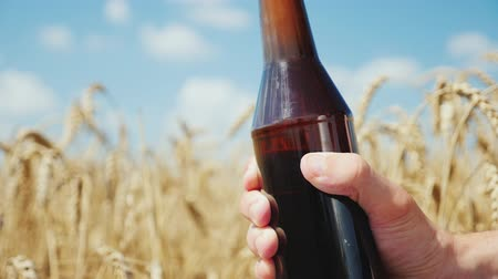 bira fabrikası : A man opens a bottle of cold beer against the background of a field of yellow wheat. Natural organic product concept