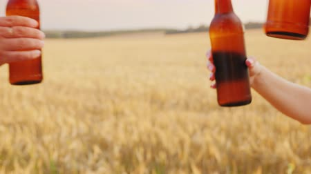 şerefe : A group of friends clink glasses of beer bottles against the background of a yellow wheat field. Celebrating the harvest and party concept