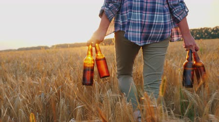 jóquei : A woman carries four bottles of cool beer, walks the field of wheat. Mens fantasy concept Stock Footage