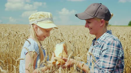 útil : A woman farmer and a girl break a loaf of bread on a wheat field. Generous vintage concept