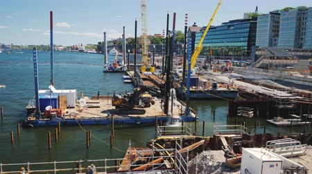 culvert : Stockholm, Sweden, July 2018: Large-scale construction on the river bed in Stockholm. On the platform there is construction equipment, pumping out of water. Against the background of the cityscape Stock Footage