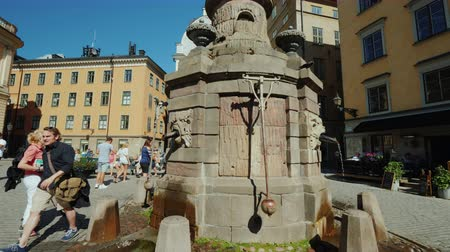 İsveççe : Stockholm, Sweden, July 2018: Fountain with drinking water in the old city of Stockholm. Nearby tourists walk, a popular holiday destination