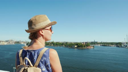 посещающий : The woman admires the beautiful view of the lake and the islands of Stockholm. Travel to Scandinavia concept