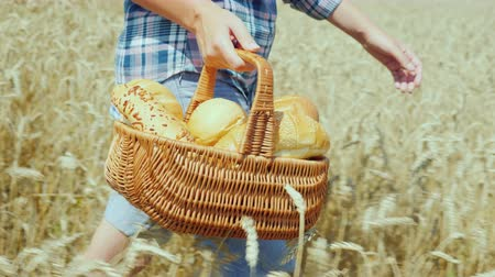 cereal product : A young woman farmer carries in a wicker basket freshly baked bread made from wheat flour from an environmentally friendly own grain production