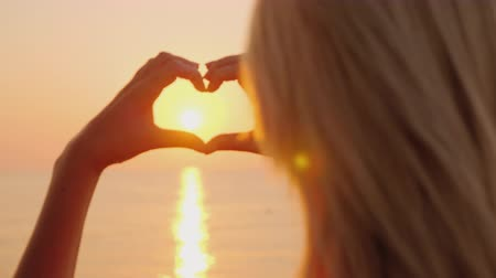 amor : A woman shows a heart sign over the sea, where the sun rises. Pink shade of water, love the sea and vacation concept Stock Footage