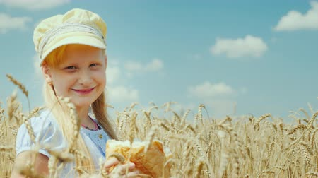 закалки : A girl with a loaf of bread stands on a wheat field, looks at the camera