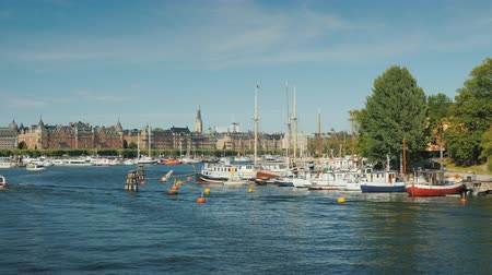 İsveççe : Quay in Sokholm, beautiful yachts are moored, boats with tourists are swimming. Beautiful European city, the capital of Sweden