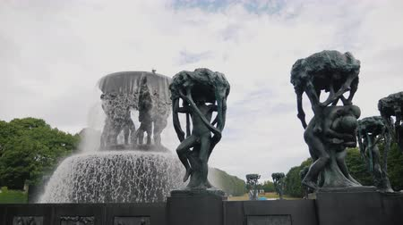 obelisk : Oslo, Norway, July 2018: A large fountain with perimeter sculptures in Sculpture Park Gustav Vigeland. Rainy weather Stock Footage