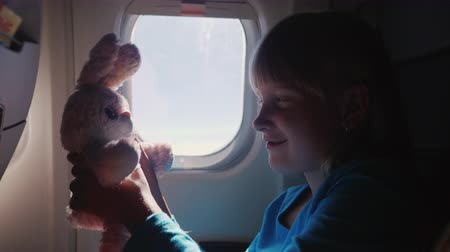 króliczek : The girl is traveling on a plane with her favorite toy. Happy childhood and vacation with the baby concept