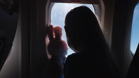 кролик : The child, together with the toy hare, looks through the airplane window. Vacation with a child and travel concludes