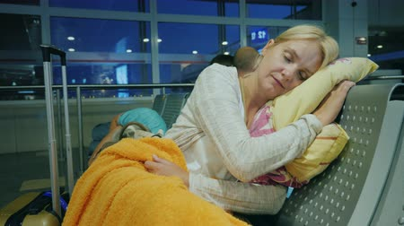 cancellation : The tired woman sleeps in the terminal of the airport. Cancellation or delay of the flight concept Stock Footage