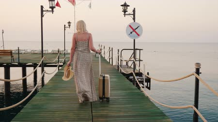 vanity : A woman with a bag on wheels rides the pier towards the sea, the rising sun beautifully illuminates her dress. Go on a cruise concept