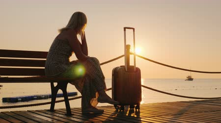 sending : A woman with a travel bag sits on a wooden pier, looking forward to the dawn over the sea and a ship in the distance. Dream of travel and freedom concept