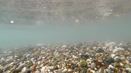 inferior : The sea surf fires pebbles in different directions. The video was shot under the water