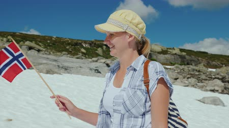 まだ : Woman with the flag of Norway on a snowy peak. Summer, the snow has not melted yet. Tourism and travel around Scandinavia