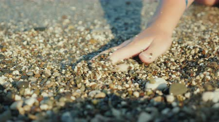 текущий : A womans hand is looking for something in shallow pebbles on the edge of the sea Стоковые видеозаписи