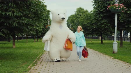 bolsa : A young stylish girl is pleased with a good shopping together with her friend the big polar bear, they are cheerfully carrying the full packages of purchases
