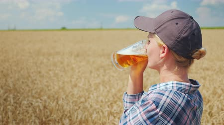 bira fabrikası : Woman farmer drinking cool beer on wheat field